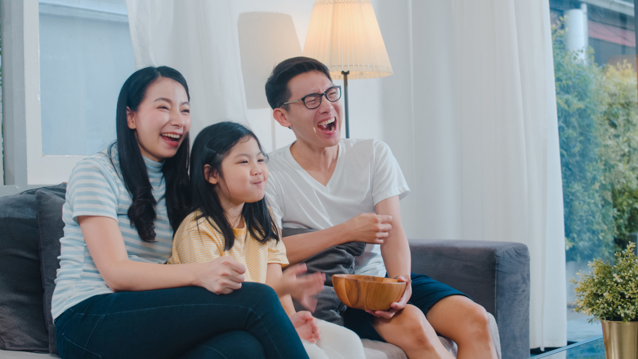 Asian family enjoy their free time relax together at home. Lifestyle dad, mom and daughter watch TV together in living room in modern home at night concept.